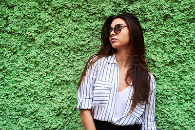 Buy stock photo Cropped shot of an attractive young woman looking away while standing against a green wall during the day