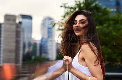 Buy stock photo Cropped portrait of an attractive young woman standing on a balcony outdoors during the day