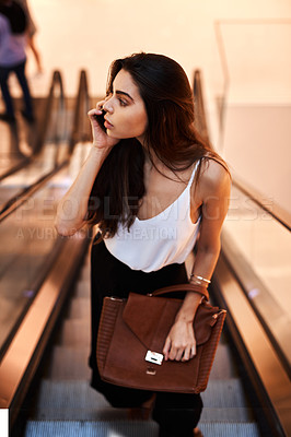 Buy stock photo Cropped shot of an attractive young woman taking a phonecall while standing on an escalator during the day