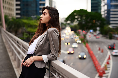 Buy stock photo Cropped shot of an attractive young woman leaning against a balcony in the city during the day