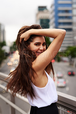 Buy stock photo Cropped portrait of an attractive young woman smiling while standing on a balcony in the city