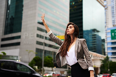 Buy stock photo Cropped shot of an attractive young businesswoman hailing for a cab in the city during the day