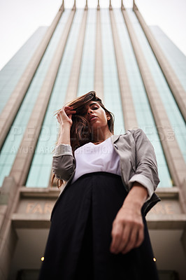 Buy stock photo Low angle portrait of an attractive young woman standing outdoors in the city