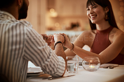 Buy stock photo Cropped shot of a young couple holding hands during their date at a restaurant