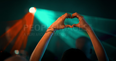 Buy stock photo Cropped shot of an unrecognizable woman making a heart shape during a concert in a nightclub