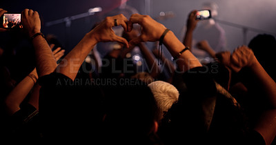 Buy stock photo Rearview shot of an unrecognizable man making a heart shape while standing in the crowd at a concert at night