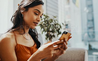 Buy stock photo Shot of a young woman using a smartphone while relaxing on the sofa at home