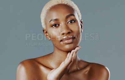 Buy stock photo Cropped shot of an attractive young woman standing alone with her hand on her face against a gray studio background