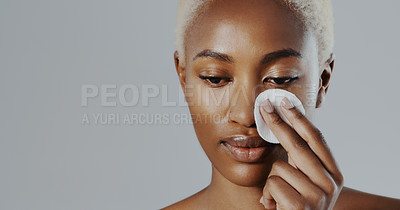 Buy stock photo Cropped shot of an attractive young woman standing alone and applying a toner with a cotton pad in the studio