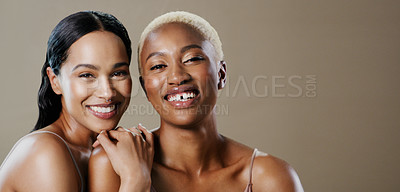 Buy stock photo Studio portrait of two attractive young women posing together and smiling while standing against a grey background
