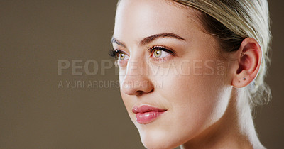 Buy stock photo Studio shot of a attractive young woman looking into the distance while standing against a grey background