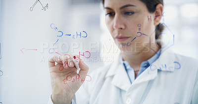 Buy stock photo Shot of a young scientist drawing molecular structures on a glass wall in a lab