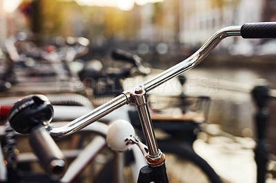 Buy stock photo Still life shot of a bicycle outdoors near a canal in the city of Amsterdam in Netherlands