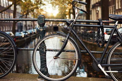 Buy stock photo Still life shot of bicycles slanted on a railing near a canal in Amsterdam, Netherlands