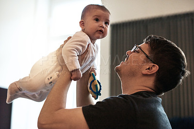 Buy stock photo Shot of a happy young father bonding and spending time with his infant daughter at home
