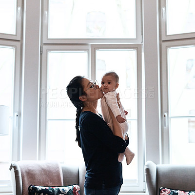 Buy stock photo Shot of a happy young mother spending time and bonding with her infant daughter at home