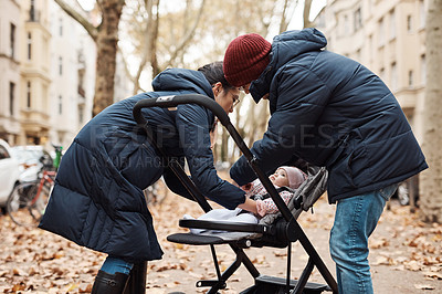 Buy stock photo Shot of a young couple putting their infant daughter in her pram outdoors in the city