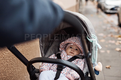 Buy stock photo Cropped shot of an adorable baby girl getting pushed inside her pram by her father outdoors