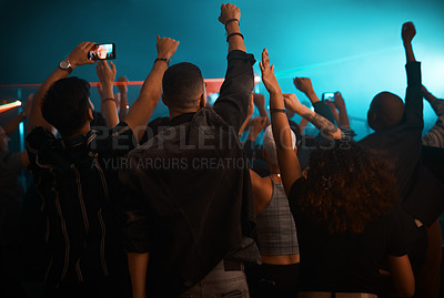 Buy stock photo Rearview shot of unrecognizable people enjoying a concert in a nightclub