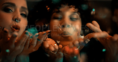 Buy stock photo Closeup shot of two girlfriends blowing confetti while partying in a nightclub