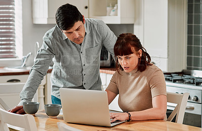 Buy stock photo Shot of a woman using a laptop with her husband standing beside her