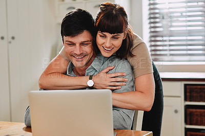 Buy stock photo Shot of a man using his laptop while being embraced by his wife at home