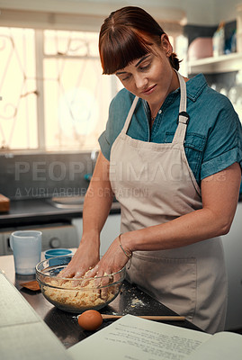 Buy stock photo Shot of an attractive young woman reading a recipe from a book while baking at home