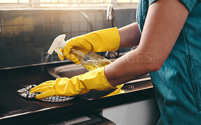 Buy stock photo Cropped shot of an unrecognizable woman using cleaning detergent to clean her kitchen at home