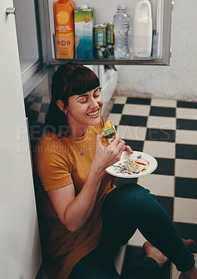 Buy stock photo Shot of an attractive young woman sitting on the floor and eating cake inside her kitchen at home