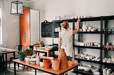 Buy stock photo Cropped shot of an unrecognizable woman standing and organising her pottery on a shelf in her workshop