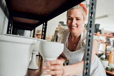 Buy stock photo Cropped shot of an attractive mature woman standing and organising her pottery on a shelf in her workshop