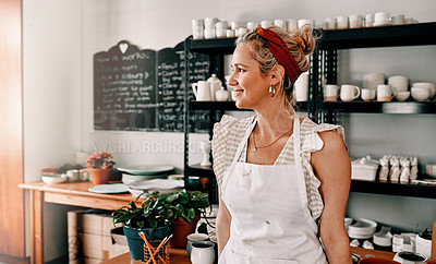 Buy stock photo Cropped shot of an attractive mature woman standing alone in her pottery workshop during the day