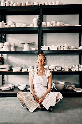 Buy stock photo Full length portrait of an attractive mature woman sitting contently on the floor alone in her pottery workshop