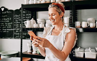Buy stock photo Cropped shot of an attractive mature woman standing alone and using her cellphone in her pottery workshop