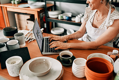 Buy stock photo Cropped shot of an attractive mature woman sitting alone and using her laptop in her pottery workshop
