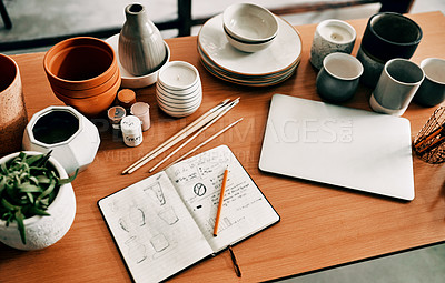 Buy stock photo High angle shot of a potter's sketches in a notebook and her laptop on a work desk in her workshop