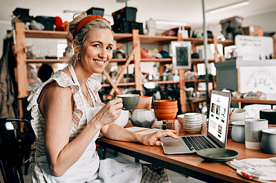 Buy stock photo Cropped portrait of an attractive mature woman sitting alone and using her laptop in her pottery workshop while drinking coffee