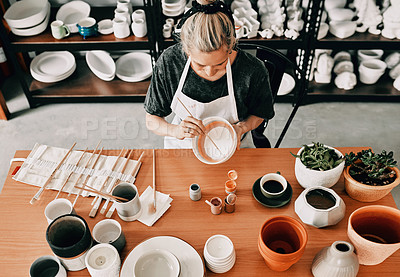 Buy stock photo High angle shot of an unrecognizable woman sitting alone and painting a pottery bowl in her workshop
