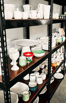 Buy stock photo Cropped shot of a potter's ceramic collection neatly arranged on a shelf in her studio