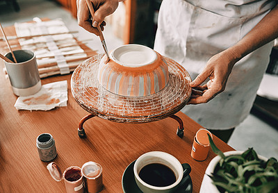Buy stock photo Cropped shot of an unrecognizable woman standing alone and painting a pottery bowl in her workshop