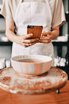 Buy stock photo Cropped shot of an unrecognizable woman standing and taking a picture of her pottery with her cellphone in her workshop