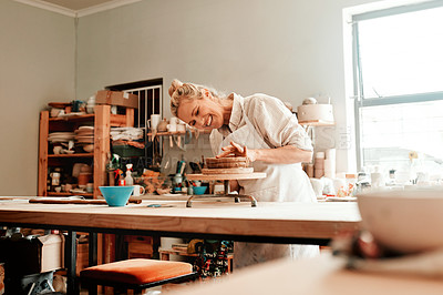 Buy stock photo Shot of a female artisan working in her pottery workshop