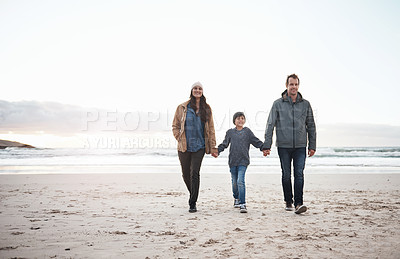 Buy stock photo Full length shot of a happy young family holding hands and walking along the beach together during a day out