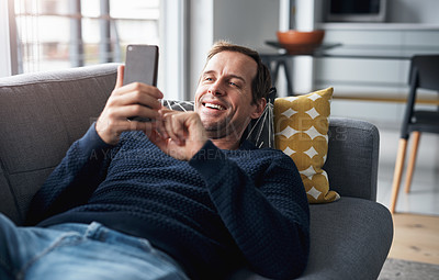 Buy stock photo Cropped shot of a handsome young man lying down on his sofa at home and using his cellphone