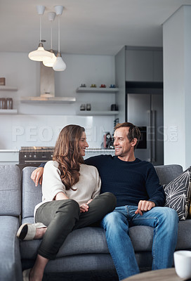 Buy stock photo Cropped shot of an affectionate young couple sitting together on their sofa at home during a day off