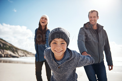 Buy stock photo Cropped portrait of a happy young boy feeling playful and pulling his parents along the beach during a day out