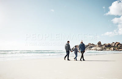 Buy stock photo Full length shot of a family holding hands and walking along the beach together during a day out