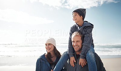 Buy stock photo Cropped shot of a handsome young man standing near his wife with his son on his shoulders at the beach