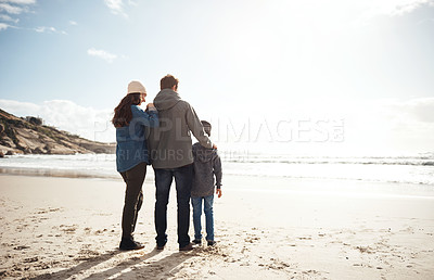 Buy stock photo Full length shot of an unrecognizable family standing close together during a day out on the beach