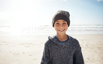 Buy stock photo Cropped portrait of a happy young boy standing alone during a day out on the beach